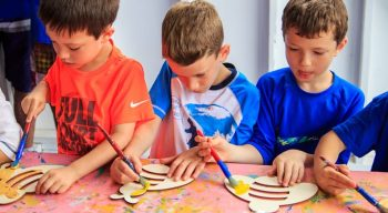 Boys painting wooden bumblebee decorations